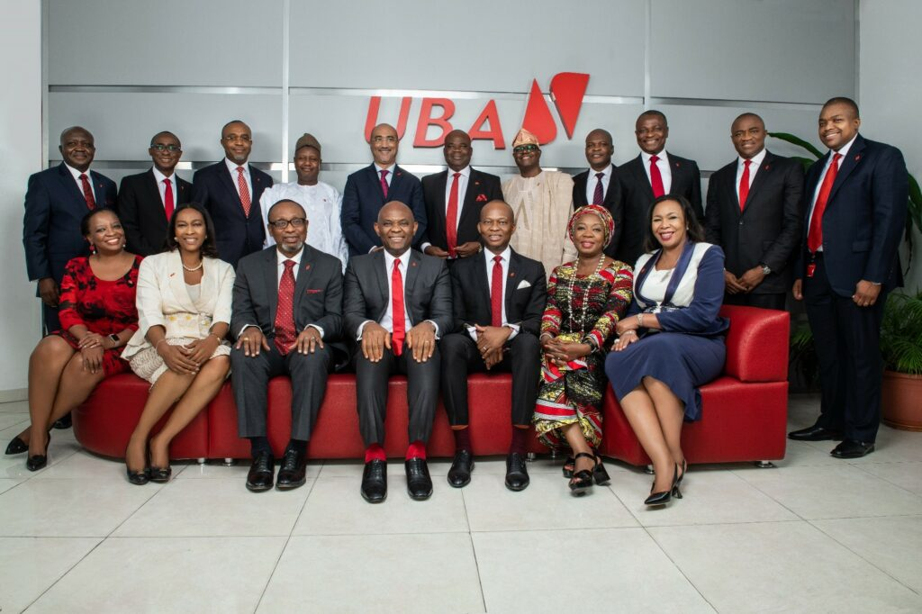 Leadership team of UBA, dressed formally with men in red ties and women in dresses against a gray background